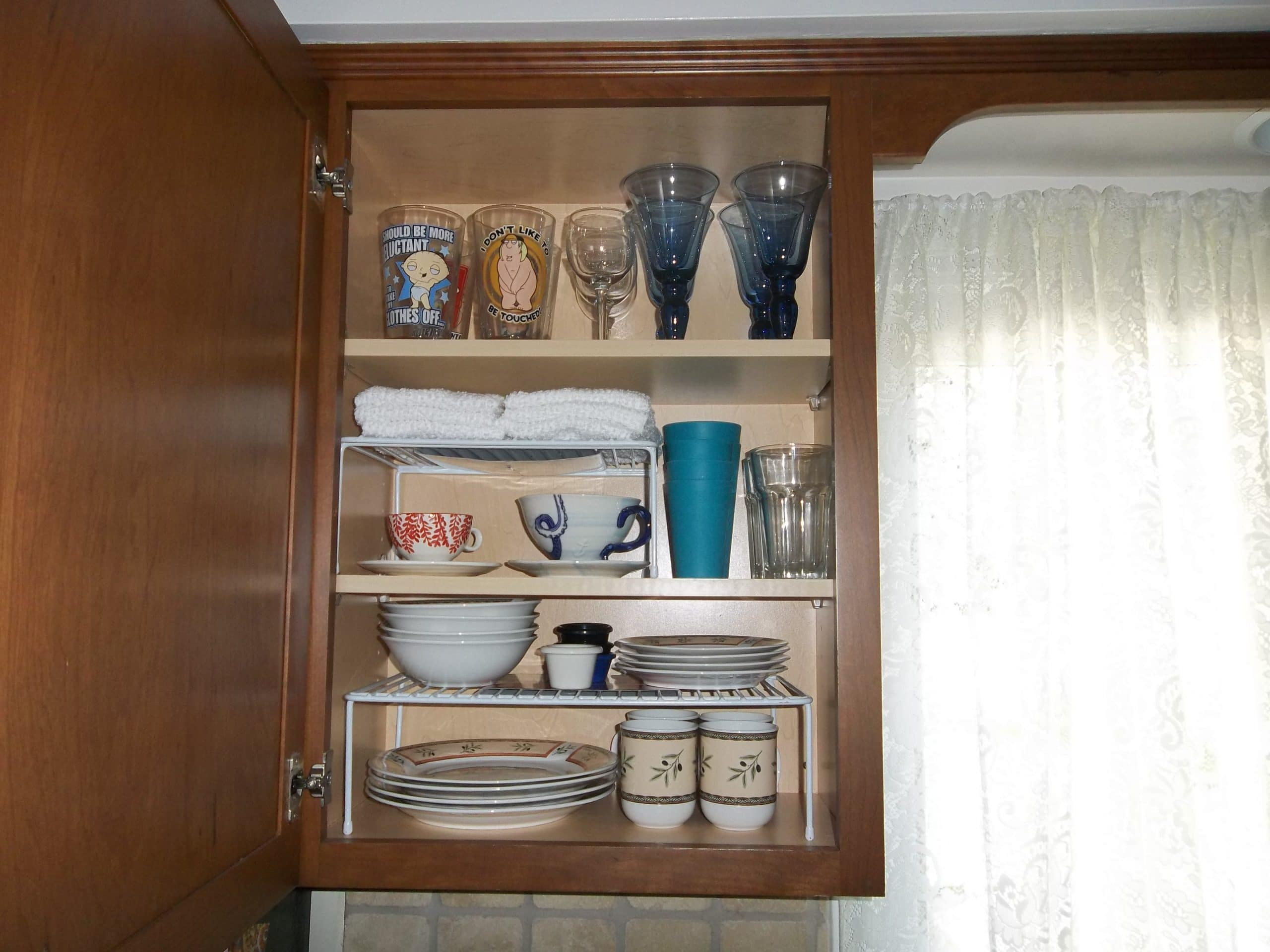 This is our dish cabinet nice and neat with the white cabinet organizers.