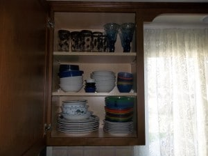 A disorganized mess of plates in our cabinet before we organized them.