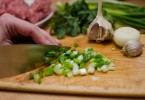 Sliced green onions with garlic in background