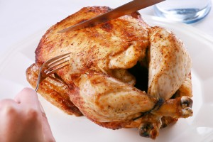 Hands carving rotisserie chicken with fork and knife