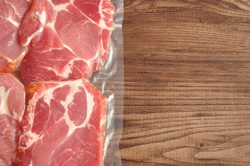 Vacuum packed meat displayed on a wooden background