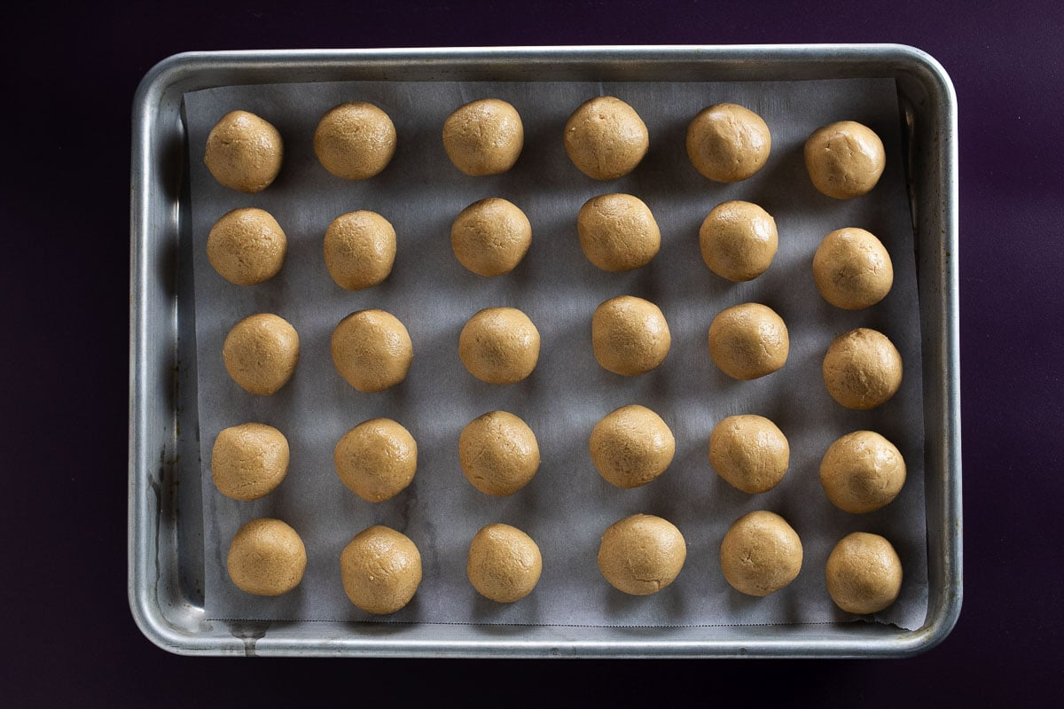 Peanut butter balls formed and placed on a cookie sheet.