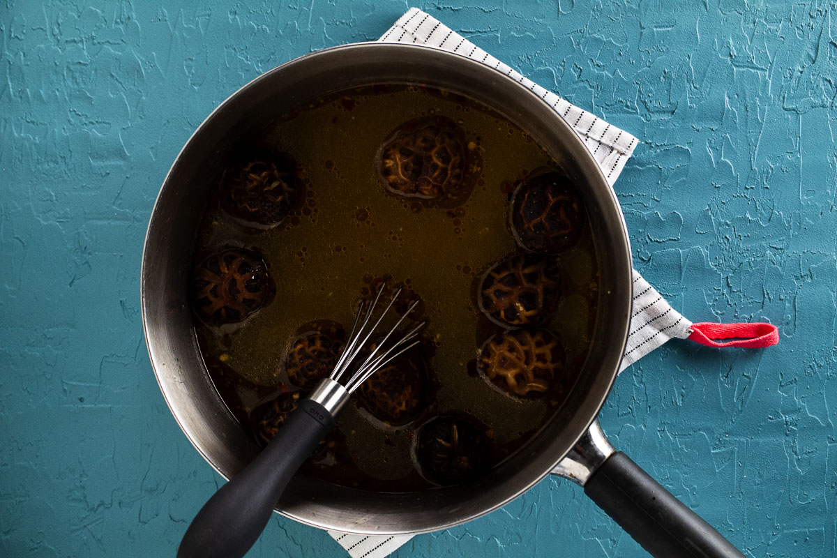 This is the broth in a pot with mushrooms.